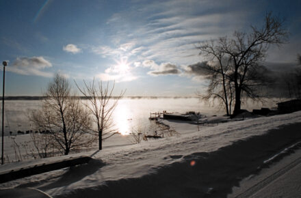 Winter scene of Cayuga Lake with snow and ice as filtered sun shines across the lake