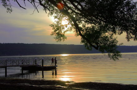 Couple on dock at Stewart Park, City of Ithaca at sunset