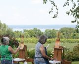 Artists painting at a winery along Cayuga Lake with vineyard and lake in the background