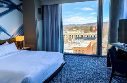 Ithaca Marriott Downtown on the Commons Photo showing a guest room with view of the Ithaca Commons through the floor to ceiling windows. A portion of the bed is in the view.
