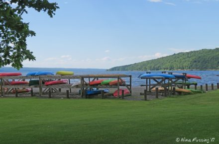 Paddlecraft Storage At Myers Park looking out toward the lake kayaks of red, yellow, blue and orange in the racks