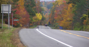 Red car driving along the Cayuga Lake Scenic Byway in the fall with leaves turning colors