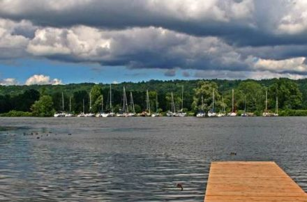 View of the Cayuga Inlet with boats docked at slips along the inlet under a partly cloudy blue sky