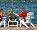 Two Visitors Toasting with glasses of wine sitting on a Boat Dock along Cayuga Lake
